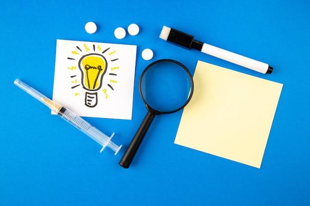 Draufsicht glühbirne zeichnung mit lupeninjektion und pillen auf blauem hintergrund krankenhausgesundheit covid-lab science pandemie-virus-medikament
