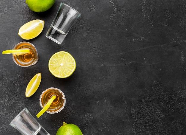 Draufsicht gold tequila aufnahmen und limette mit kopierraum