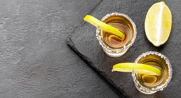 Draufsicht gold tequila schüsse und limette mit salz