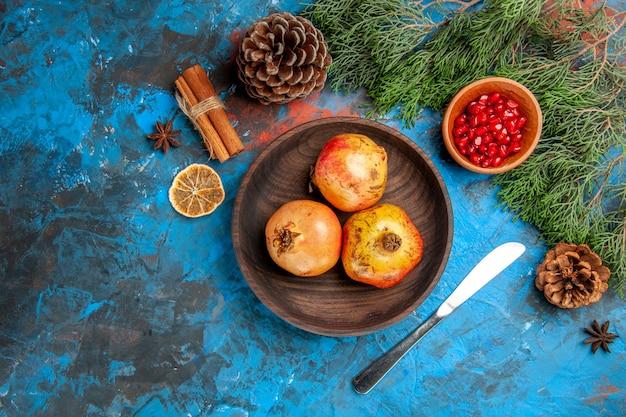 Draufsicht granatäpfel auf holzplatte granatapfelkerne in holzschale auf blauem hintergrund