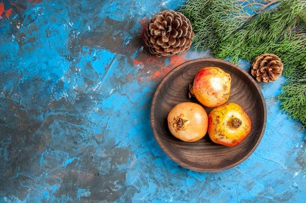 Draufsicht granatäpfel auf holzplatte kiefernzweig und zapfen auf blauer oberfläche