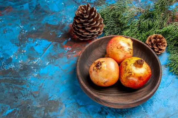 Draufsicht granatäpfel auf holzplatte tannenzweig und zapfen auf blauem hintergrund