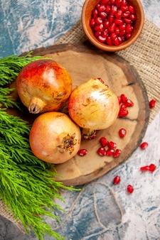 Draufsicht granatäpfel auf rundem schneidebrett granatapfelkerne in schüssel auf blau-weißem hintergrund