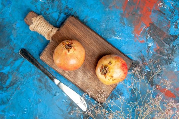 Draufsicht granatäpfel auf schneidebrett abendessenmesser auf blauem abstraktem hintergrund