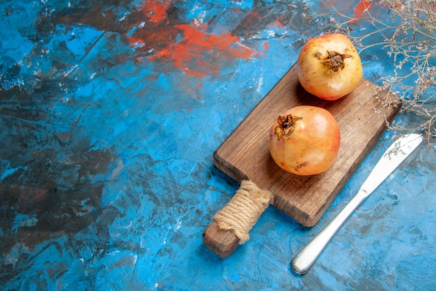 Draufsicht granatäpfel auf schneidebrettmesser auf blauem hintergrund