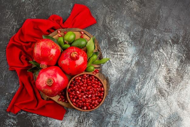 Draufsicht granatäpfel drei granatapfel granatapfelkerne auf dem brett auf der roten tischdecke