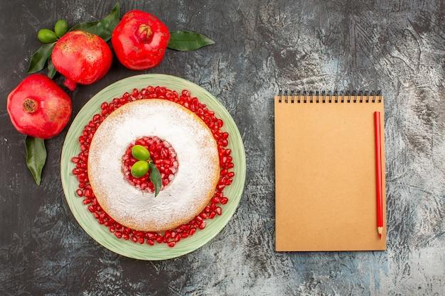 Draufsicht granatäpfel ein appetitlicher kuchen drei granatäpfel mit blättern notizbuch und bleistift