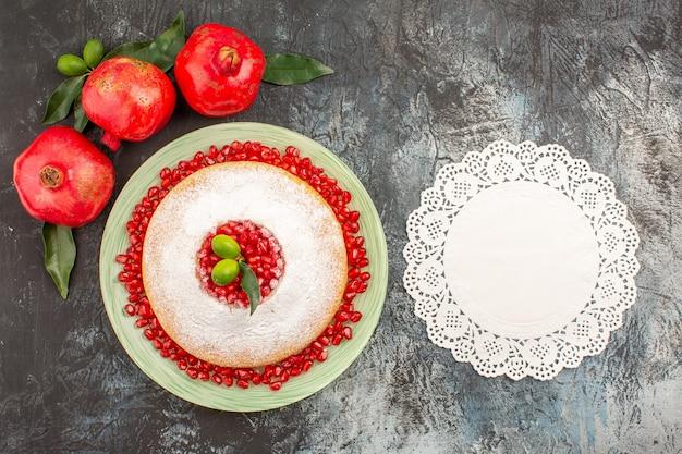 Draufsicht granatäpfel ein appetitlicher kuchen drei granatäpfel mit blättern und weißem spitzendeckchen