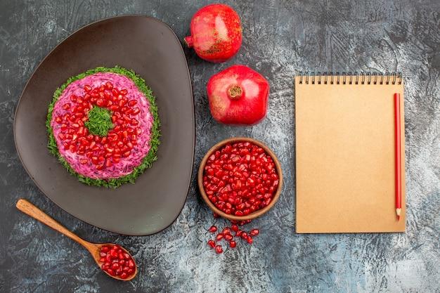 Draufsicht granatäpfel granatapfelkerne löffel ein appetitliches gericht bleistift notizbuch