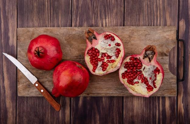 Draufsicht granatäpfel mit einem messer auf einem schneidebrett auf einem holztisch