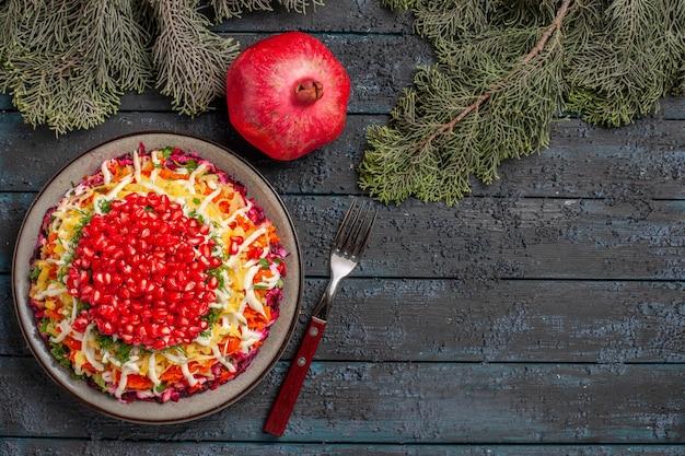 Draufsicht granatapfel appetitliches gericht aus granatapfel in teller neben den granatapfel- und fichtenzweigen