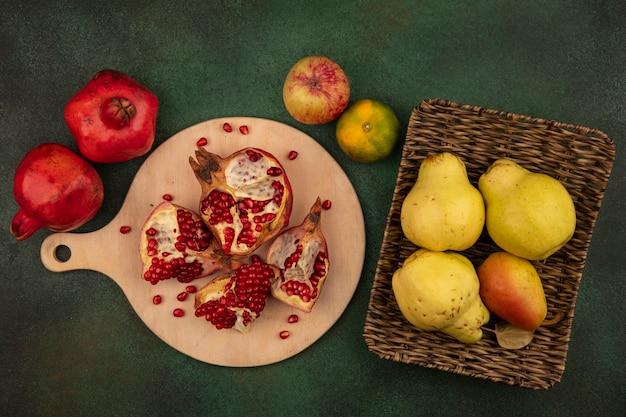 Draufsicht granatapfelscheiben auf schneidebrett mit birnen im korb