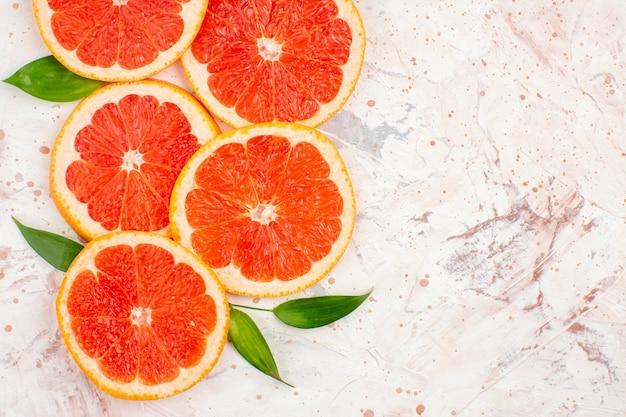 Draufsicht grapefruits scheiben mit blättern auf nackter oberfläche mit kopierraum