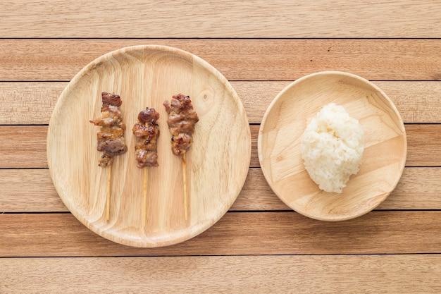 Draufsicht grillte schweinefleisch mit bambusstock und thailändischem klebrigem reis auf hölzernem teller