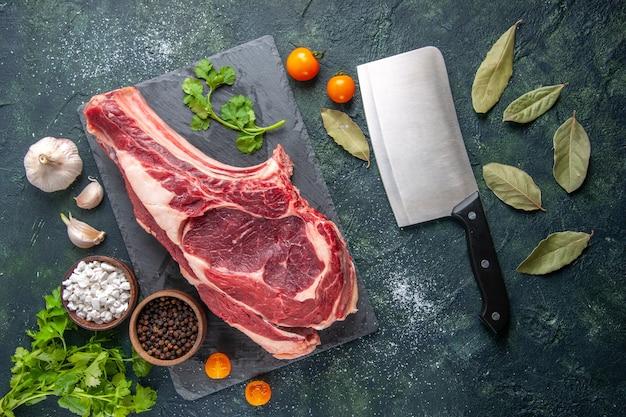Draufsicht große fleischscheibe rohes fleisch mit pfeffer und grüns auf dunkler oberfläche