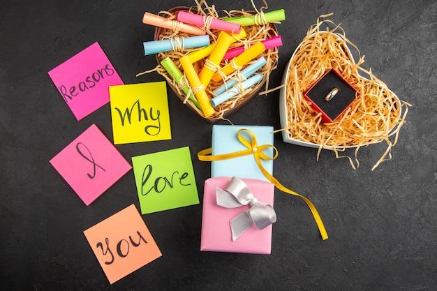 Draufsicht gründe, warum ich dich liebe, geschrieben auf farbigen haftnotizen, blättern sie wunschpapiere in einer schachtel geschenk-verlobungsring auf dem tisch