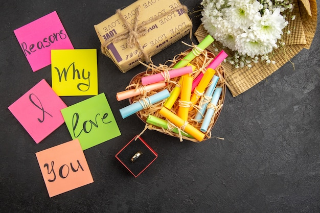 Draufsicht gründe, warum ich dich liebe, geschrieben auf farbigen haftnotizen scroll wunschpapiere in box blumenstrauß ring geschenk auf dem tisch