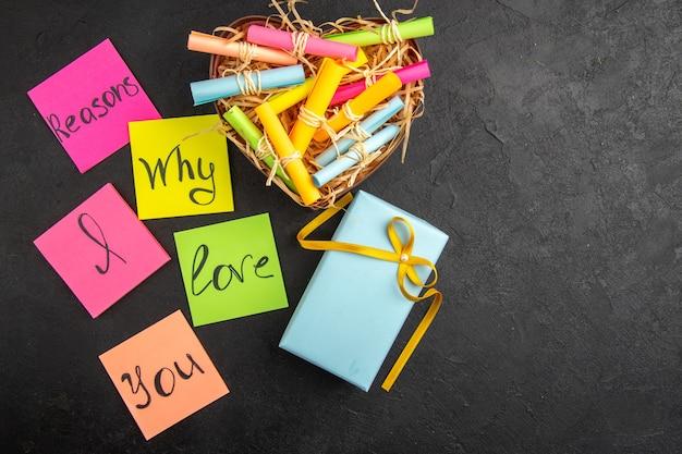 Draufsicht gründe, warum ich dich liebe, geschrieben auf farbigen haftnotizen, scrolle wunschpapiere in box geschenk auf tisch freiraum