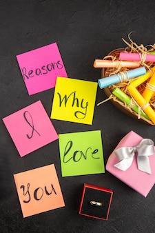 Draufsicht gründe, warum ich dich liebe, geschrieben auf farbigen haftnotizen, scrolle wunschpapiere in einer schachtel verlobungsring auf dem tisch