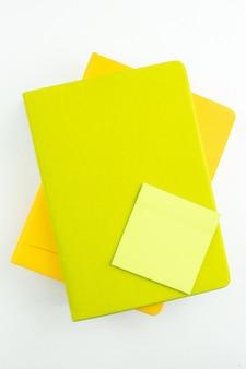Draufsicht grüne haftnotiz auf bunten notizbüchern auf weißem tisch