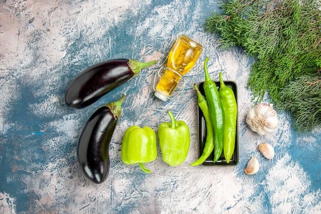 Draufsicht grüne peperoni auf schwarzem teller knoblauchöl auberginen paprika auf blau-weißem hintergrund