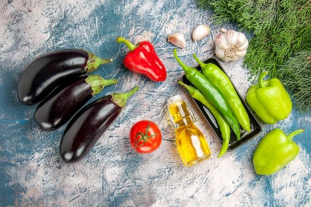 Draufsicht grüne peperoni auf schwarzem teller mit knoblauch und roten paprika auf blau-weißem hintergrund