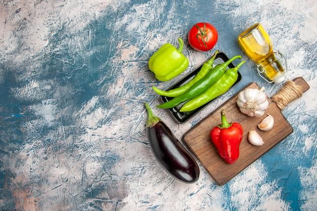 Draufsicht grüne peperoni auf schwarzem teller tomaten rote und grüne paprika knoblauch auf schneidebrett aubergine auf blau-weißem hintergrund