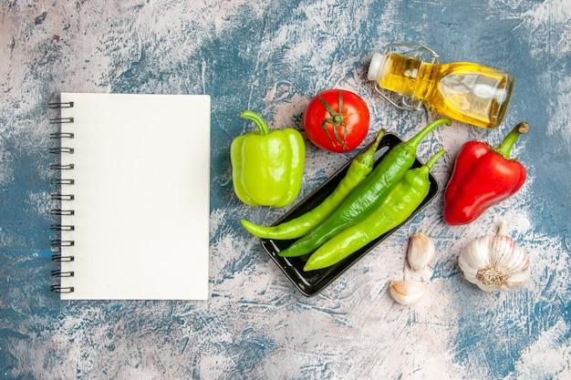Draufsicht grüne peperoni auf schwarzem teller tomaten rote und grüne paprika knoblauch ein notizbuch auf blau-weißem hintergrund