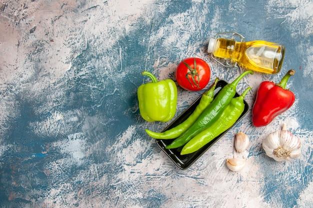 Draufsicht grüne peperoni auf schwarzem teller tomaten rote und grüne paprika knoblauchölflasche auf blau-weißem hintergrund