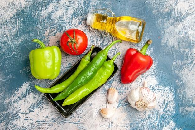 Draufsicht grüne peperoni auf schwarzem teller tomaten rotes und grünes paprika knoblauchöl auf blau-weißem hintergrund
