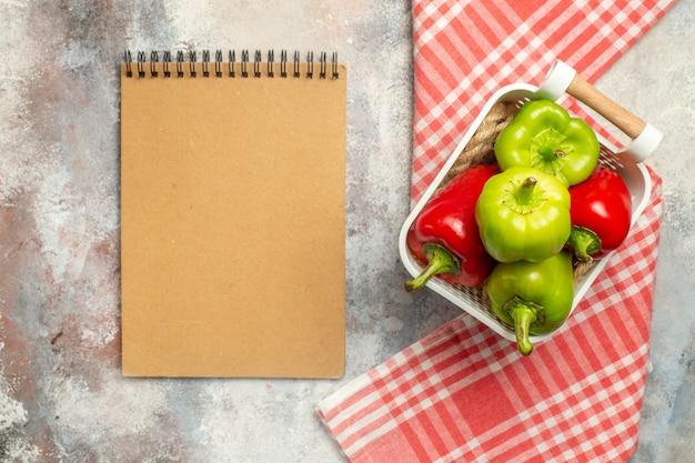 Draufsicht grüne und rote paprikaschoten im plastikkorb eine rote tischdecke des notizbuchs auf nackter oberfläche