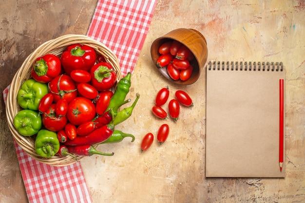 Draufsicht grüne und rote paprikaschoten tomaten in weidenkorb verstreute kirschtomaten aus schüssel küchentuch ein notizbuch und roter bleistift auf bernsteinfarbenem hintergrund