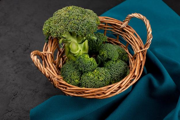 Draufsicht grüner brokkoli im korb auf dem dunklen boden