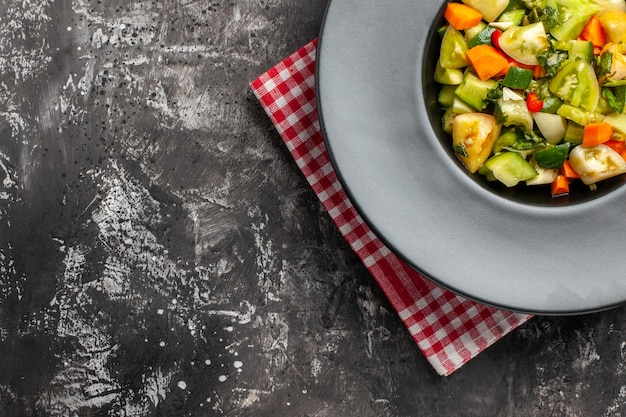 Draufsicht grüner tomatensalat auf ovalem teller auf serviette auf dunklem hintergrund