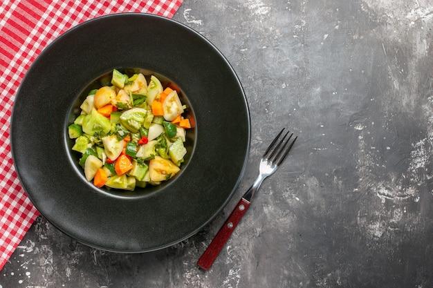 Draufsicht grüner tomatensalat auf ovalem teller eine gabel auf dunklem hintergrund