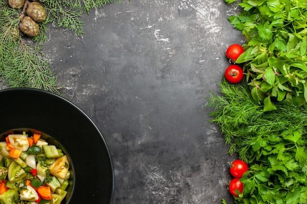 Draufsicht grüner tomatensalat auf ovalem teller grünt tomaten auf dunklem hintergrund