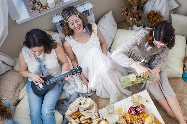 Draufsicht-gruppe der hippie-frau, die zeit zusammen auf der junggesellenparty verbringt, die singendes lied lächelnd isst