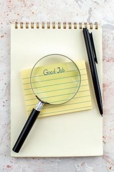 Draufsicht gute arbeit auf haftnotiz auf notizbuchstift lupa auf tisch geschrieben