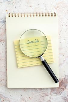 Draufsicht gute arbeit auf haftnotiz lupa auf notizblock auf tisch geschrieben