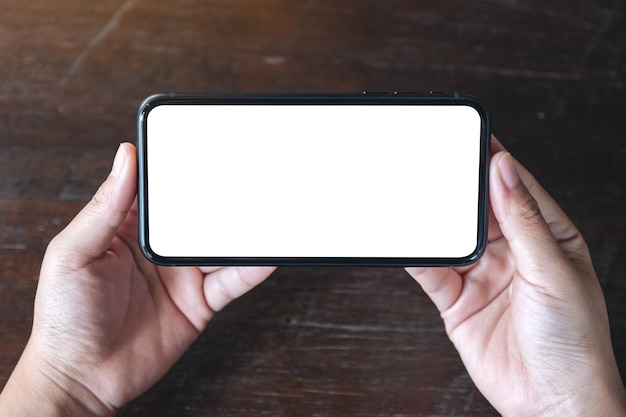 Draufsicht hände, die schwarzes handy mit leerem desktop-bildschirm horizontal auf hölzernem tischhintergrund halten