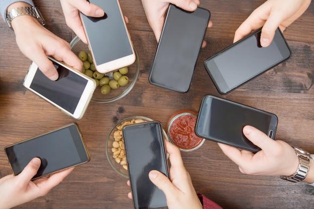 Draufsicht hände kreisen mit telefon im café ein
