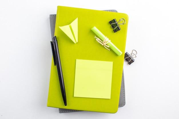 Draufsicht haftnotizen binder clips auf notizblöcken schwarzer stift papierflieger auf weißem hintergrund