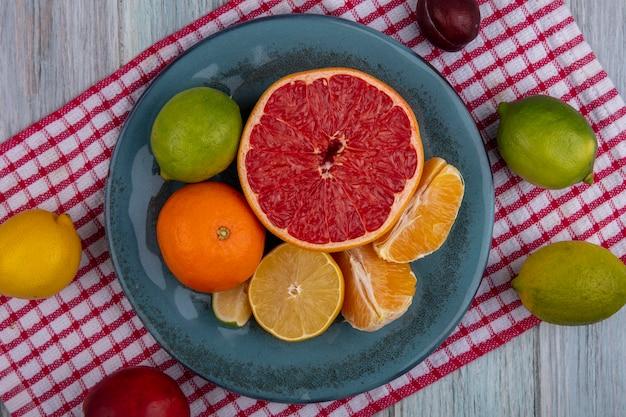 Draufsicht halbe grapefruit mit orangen- und geschälten keilen auf einem teller mit zitronenlimetten und pfirsichen auf einem rot karierten handtuch