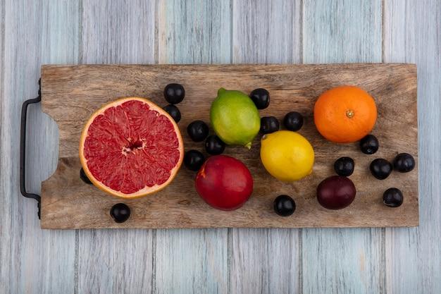 Draufsicht halbe grapefruit mit orangen-zitronen-limette und pfirsich mit kirschpflaume auf einem schneidebrett