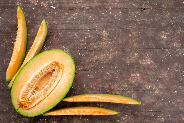 Draufsicht halbgeschnittenes melonengrün mit scheiben auf braun