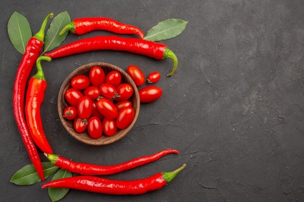 Draufsicht halbkreis von roten peperoni und lorbeerblättern und einer schüssel kirschtomaten auf der linken seite des schwarzen tisches