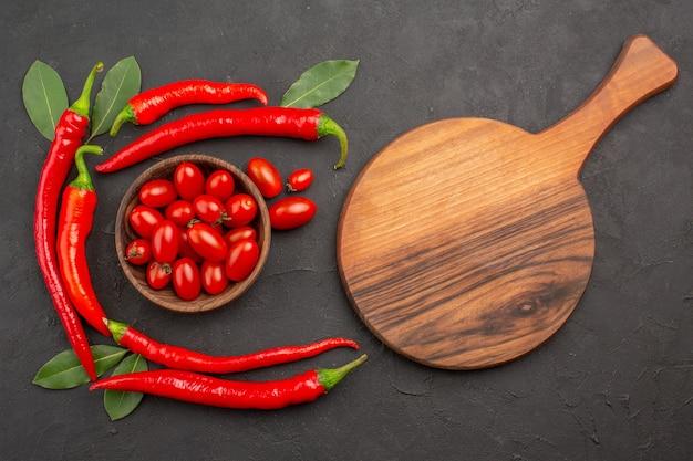 Draufsicht halbkreis von roten peperoni und lorbeerblättern und einer schüssel kirschtomaten und einem ovalen schneidebrett auf dem schwarzen tisch