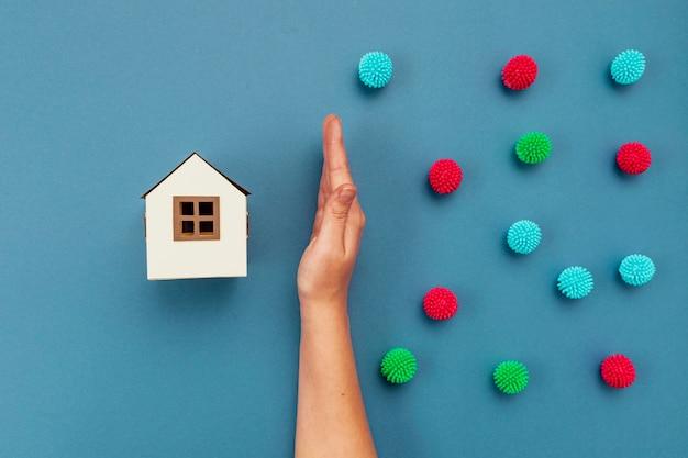 Draufsicht hand, die dekorative kugeln und papierhaus trennt
