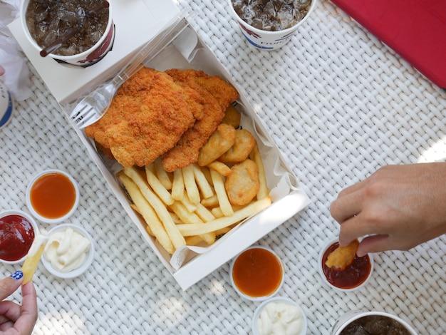 Draufsicht-hand, die nuggets in der lebensmittelbox hält frittiertes essen auf weißem tisch
