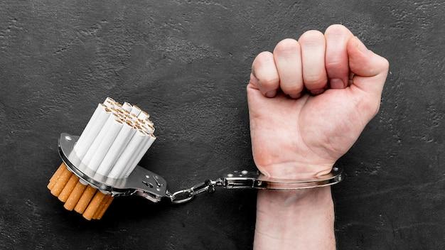 Draufsicht hand mit handschellen zigaretten